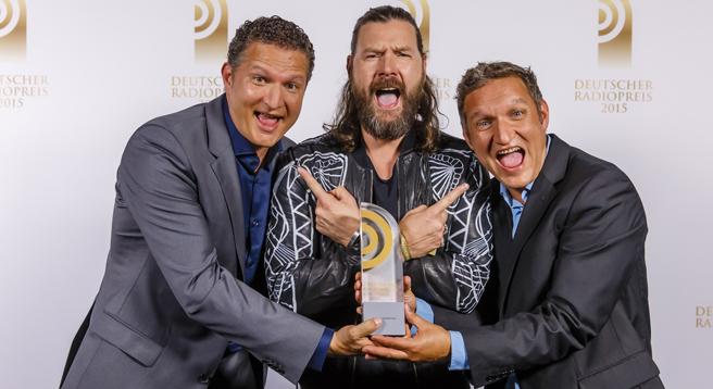 """Die Gewinner in der Kategorie """"Beste Sendung"""": Stefan Kreutzer (li.) und Stefan Schwabeneder (re.) von BAYERN 3, mit Laudator Rea Garvey"""