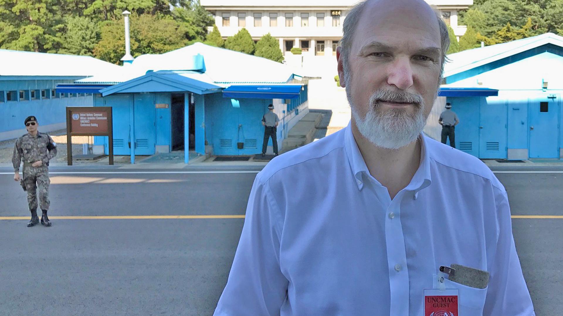 Thomas Schirrmacher vor der UN-Verhandlungsbaracke in der UN-Schutzzone in der Mitte der demilitarisierten Zone. Die Baracken stehen auf beiden Seiten der Grenze, das Gebäude im Hintergrund ist das Grenzhauptquartier der Nordkoreaner auf nordkoreanischem Boden.