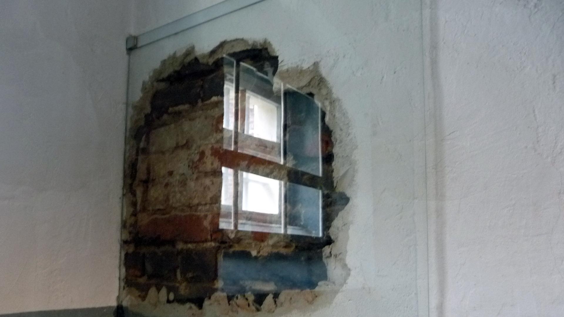 Das besagte Loch hinter Plexiglas, darin die Reflektion des Zellenfensters
