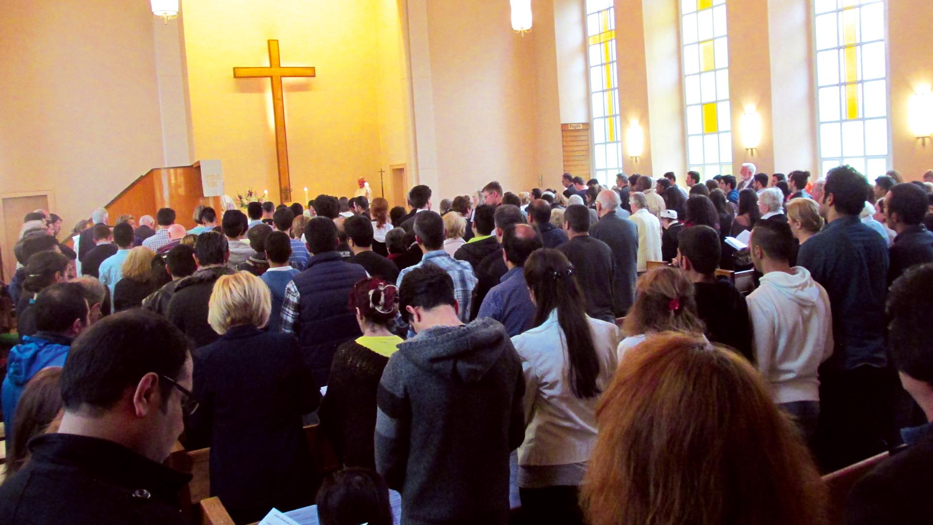 In christlichen Gemeinden, wie hier in Berlin, werden Flüchtlinge heimisch. Wie Christen mit deren Wunsch nach Taufe umgehen sollen, haben die beiden großen Kirchen bei einer Fachtagung in Münster diskutiert.