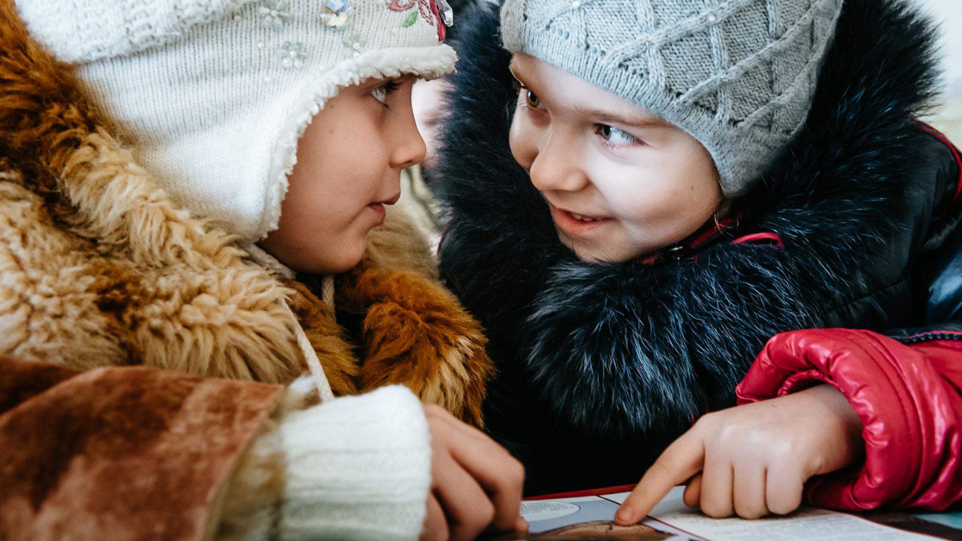 """Der Glaubenskurs """"Die größte Reise"""" fand im vergangenen Jahr weltweit statt. Diese Mädchen aus der Ukraine schauen sich ein Materialbuch an."""