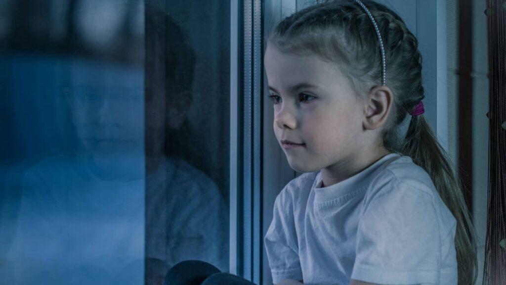 Trauriges Kind vor Fenster